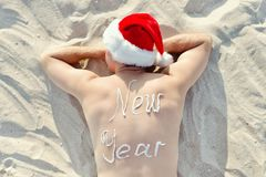 Man in Santa hats with the inscription 2018 on the back lying on Royalty Free Stock Photos