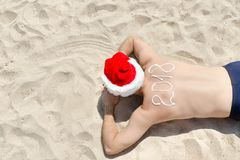 Man in Santa hats with the inscription 2018 on the back lying on Stock Images