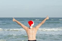 Man in Santa hats with the inscription New Year on the back on the beach. Thumbs up. Back view Stock Photo