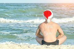 Man in Santa hats with the inscription New Year on the back is sitting on the beach. Back view Royalty Free Stock Image