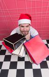 Man santa hold bags on black and white checkered floor Royalty Free Stock Photos