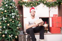 Man santa with presents at xmas tree. Macho in red hat with wrapped boxes at fireplace. Gift giving, holiday greeting. Boxing day concept. Christmas, new year Royalty Free Stock Images