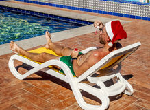 A man in a Santa's hat blows soap bubbles on the tropical resort Stock Photos