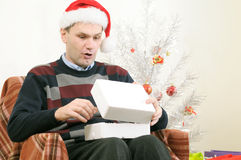 Man in Santa's hat opening Christmas gift Royalty Free Stock Photo