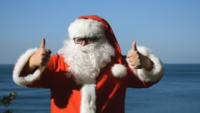 A man in a santa slaus costume on the seashore. Christmas in the tropics. A man in a Santa Claus costume on the seashore stock footage