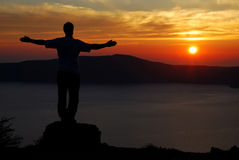 Man on Santorini sunset over the coastline royalty free stock photography