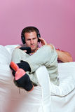 Man sat in an armchair listening to music Stock Image
