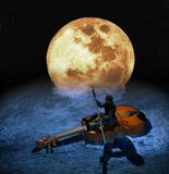 Musical Raft. Man sat on a big violin, paddling with the bow  in the water under a big yellow Moon Stock Image