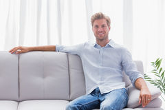 Man sat on a couch in the living room Royalty Free Stock Images