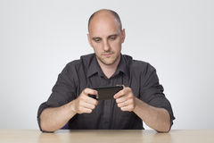 Man sat at desk playing on phone Stock Photos