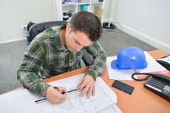 Man sat at desk working on blueprints royalty free stock photos