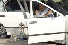 Man sat in his car smoking, Lebanon. A man sat in his car smoking a narghile pipe, Lebanon Stock Photography