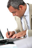 Man sat at his desk writing Stock Photography