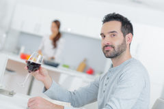 Man sat in kitchen with glass red wine Royalty Free Stock Image