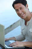 Man sat outdoors with laptop Stock Images