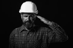 Man with satisfied face expression isolated on black background. Construction and hard work concept. Worker with brutal. Image wears white helmet and salutes royalty free stock photography