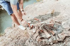 Top view of strong man wearing sneakers grilling some sausages near lake. Man with sausages. Top view of strong man wearing white comfortable sneakers grilling royalty free stock images