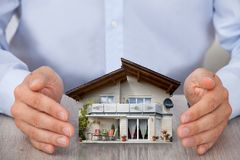 Man saving house model Stock Images