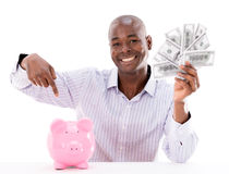Man saving money in a piggybank Royalty Free Stock Photo