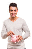 Man saving money to a piggy bank Royalty Free Stock Images