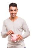 Man saving money to a piggy bank Royalty Free Stock Images