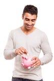 Man saving money to a piggy bank Royalty Free Stock Image