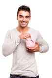Man saving money to a piggy bank Stock Photography