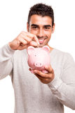 Man saving money to a piggy bank Stock Images