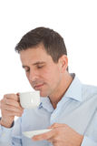 Man savouring the aroma of a cup of coffee. Good looking middle-aged man savouring the aroma of a cup of fresh hot coffee during a business break smiling  in Royalty Free Stock Images
