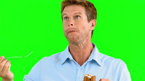 Man savouring a delicious cake on green screen stock video