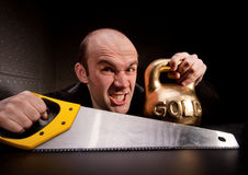 Man with saw and heavy weight of gold Stock Photos