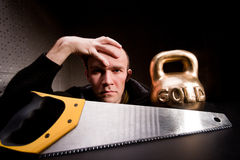Man with saw and heavy weight of gold Stock Image