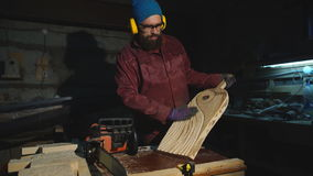 The man with the saw makes a pattern on a wooden Board stock video