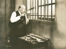 Man sawing through bars Royalty Free Stock Images