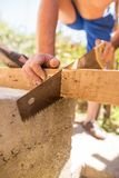 A man is sawing a beam of wood.  Royalty Free Stock Image