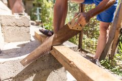 A man is sawing a beam of wood.  Royalty Free Stock Photography