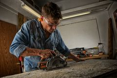 Man sawing a board. Man cutting out a section of wood with a circular saw in his work shop Stock Image