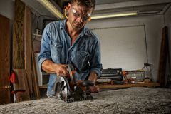 Man sawing a board. Man cutting out a section of wood with a circular saw in his work shop Royalty Free Stock Photos