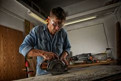 Man sawing a board. Man cutting out a section of wood with a circular saw in his work shop Stock Images