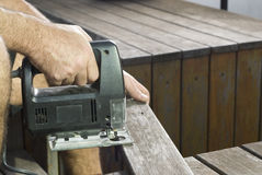 Man Sawing Board with Jigsaw - Horizontal Royalty Free Stock Photos