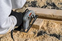 Man sawing a Board with a power tool, chips fly in all directions. Construction, wood processing. A man sawing a Board with a power tool, chips fly in all Royalty Free Stock Photo