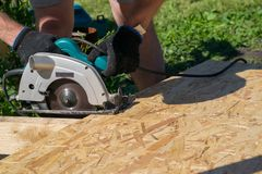 Man sawing a Board with a power tool, chips fly in all directions. Construction, wood processing. A man sawing a Board with a power tool, chips fly in all Stock Photo
