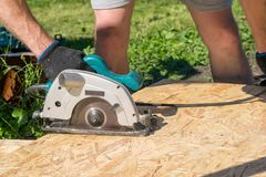 Man sawing a Board with a power tool, chips fly in all directions. Construction, wood processing. A man sawing a Board with a power tool, chips fly in all Royalty Free Stock Photos