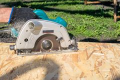 Man sawing a Board with a power tool, chips fly in all directions. Construction, wood processing. A man sawing a Board with a power tool, chips fly in all Royalty Free Stock Images