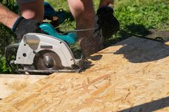 Man sawing a Board with a power tool, chips fly in all directions. Construction, wood processing. A man sawing a Board with a power tool, chips fly in all Stock Image