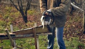 Man sawing a board. Young man sawing a board Royalty Free Stock Image