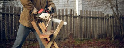 Man sawing a board. Young man sawing a board Royalty Free Stock Photography