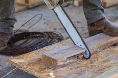 The man is sawing the boards with a chainsaw. A man using a chainsaw saws a wooden beam royalty free stock image