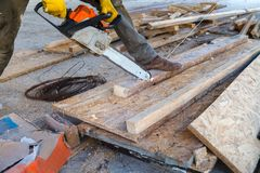 The man is sawing the boards with a chainsaw. A man using a chainsaw saws a wooden beam stock image