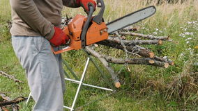 Man sawing a branch with the help of an chain saw, firewood. HD stock video footage